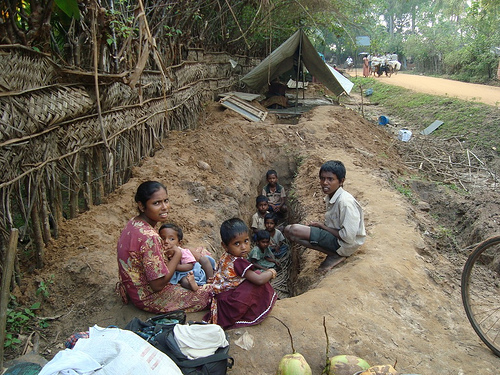 """Tamil family sit by a trench in the LTTE-occupied """"No Fire Zone"""" (Human Rights Watch)"""